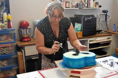 Dorita Booth hard at work airbrushing a Spiderman cake in her special cake room inside Dorita's Cafe.