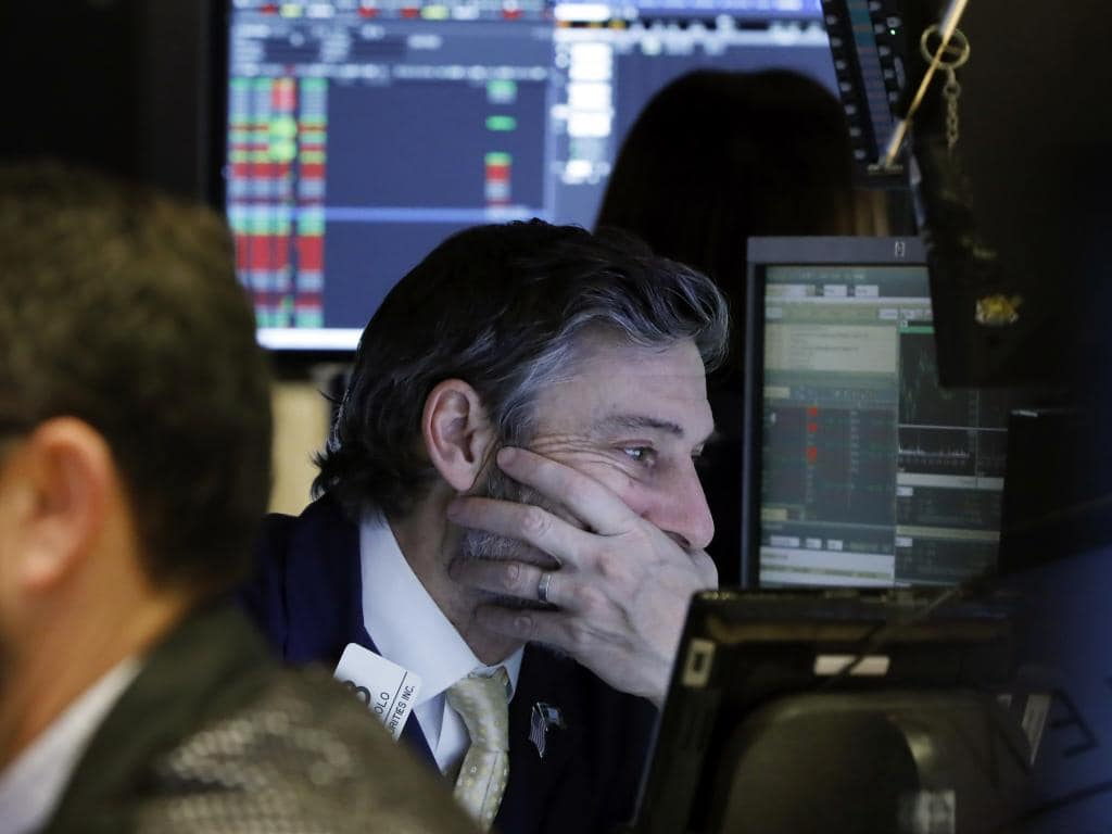Trader John Romolo works on the floor of the New York Stock Exchange. Stocks went into a steep slide Thursday after Apple sent a shudder through Wall Street with word that iPhone sales in China are falling. Picture: AP