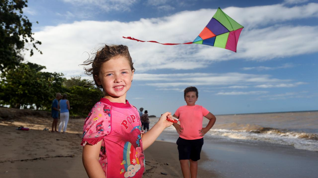 Melay Tavares, 5, and her brother Lorenzo, 8, of Holloways Beach enjoying the sunshine and strong sea breeze by flying a kite on the beach. PICTURE: STEWART MCLEAN