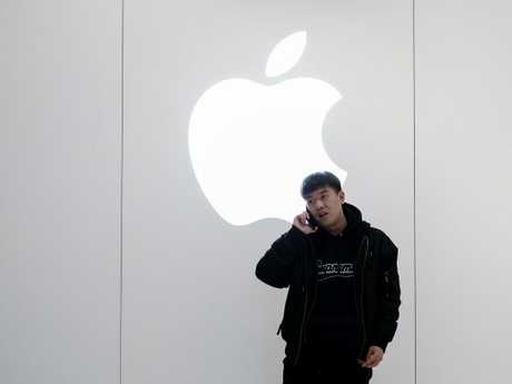A Chinese man is on the phone outside the Apple Store in Beijing, China. Picture: Getty