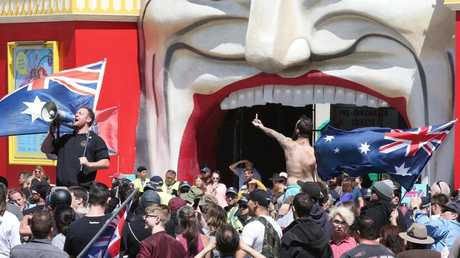 A protester addresses the crowds outside Luna Park in St Kilda. Picture: AAP
