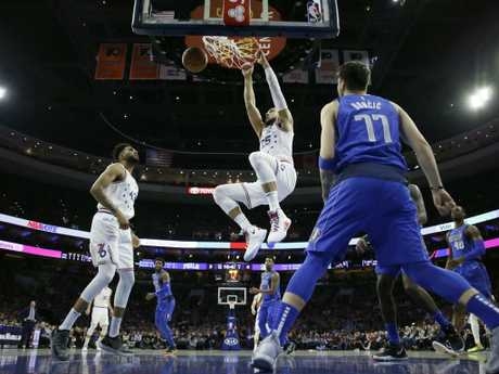 Ben Simmons throws one down hard as Jonah Bolden and Dallas rookie Luka Doncic get the best view in the house. Picture: AP
