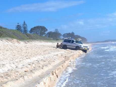 MAIN IMAGE: A 4WD enthusiast visiting Wooli gets bogged in soft sand. INSET: A 4WD vehicle on the beach at Brooms Head, where an access gate has recently been installed.