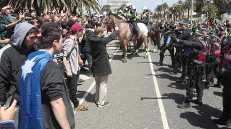 Police had to keep protesters apart on the St Kilda foreshore in Melbourne on Saturday. Picture: AAP