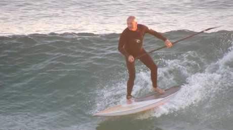 John Macnamara, 70, paddle boarding in the surf. Photo: Trevor Elms