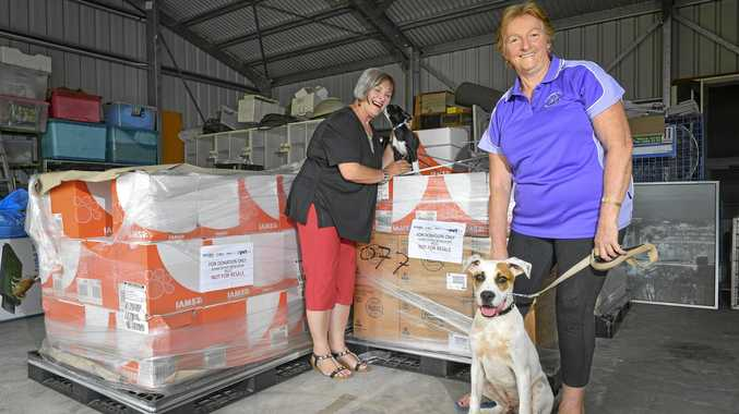 HAPPY PUPS: Judy Whicker with 8-week-old Nixon and Betty Bridge with 6-month-old Rex with just a couple of the many pallets that have been donated.