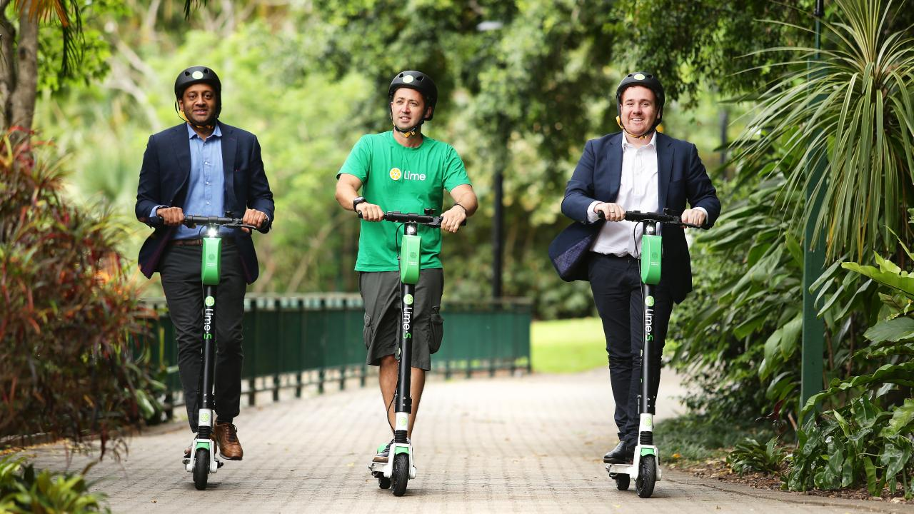Mayank Mittal, Vinicius Machado Campos and Mitchell Price, at Brisbane Botanical Gardens, launched Lime electric scooters in Brisbane. Picture: AAP/Claudia Baxter