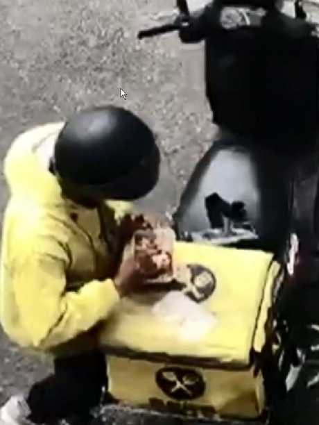 A driver is caught on camera helping himself to a food order he was supposed to deliver. Picture: Channel 9