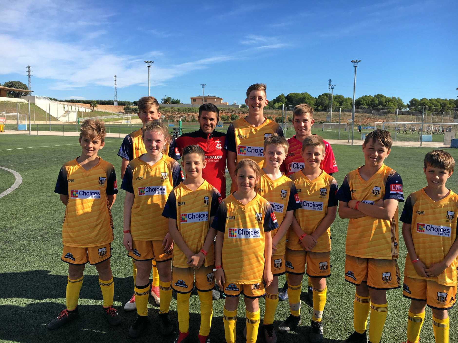 SPAIN TOUR: The Southern Downs Football Academy team (back, from left) Harry McMahon, Salou coach Marc Miquel, Declan Clegg, Lachlan Montgomery, (front) Joel Keevers, Mel Reedy, Boula Kairouz, Chloe Gaske, Jack Reedy, Hayden Gaske, Kweller and Percy Manfield at Salou field near Barcelona during last year's tour to Spain.