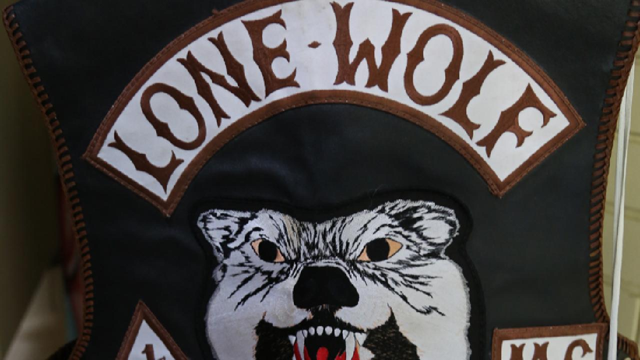 A former Lone Wolf bikie will stand trial for two alleged brutal stabbing attacks, including one in which he threatened to cut off a man's leg with a tomahawk.