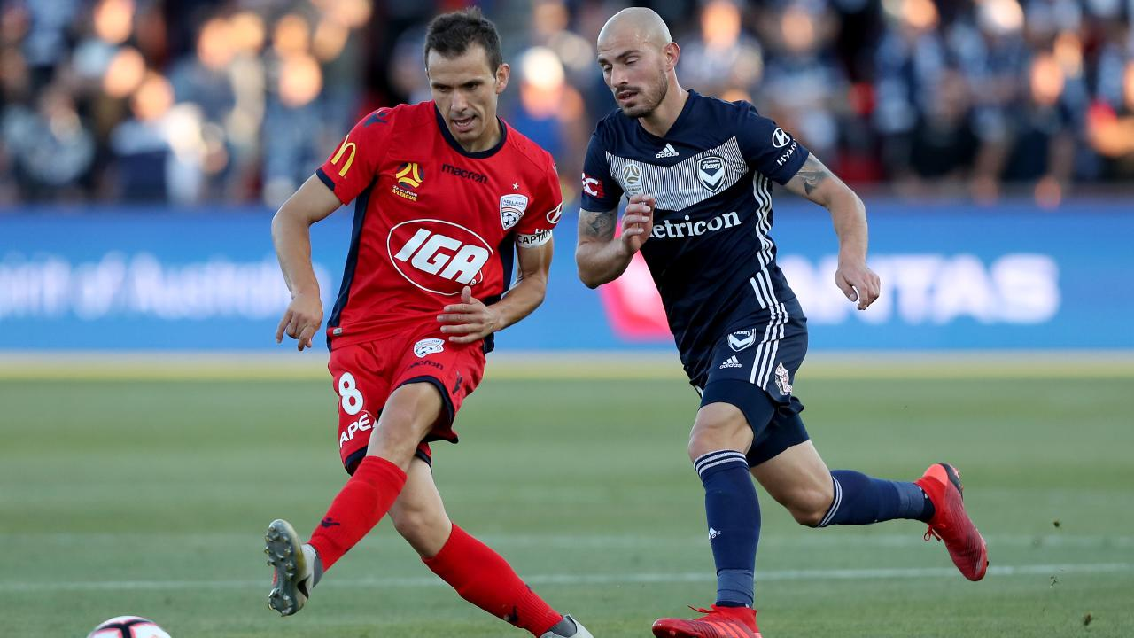 Adelaide United's Isaias passes the ball ahead of Melbourne Victory's James Troisi on Wednesday night. Picture: Getty Images