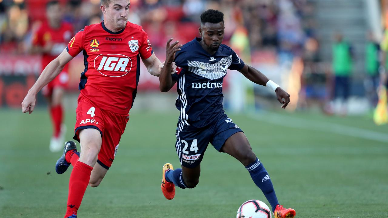 Melbourne Victory's Elvis Kamsoba (right) is challenged by Adelaide United's Ryan Strain. Picture: Getty Images