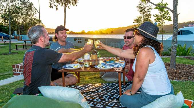 CLOCKWISE FROM LEFT: Phil Nicholas from Live Prawn Productions, Ed Goode of Two Bridges Espresso (who is providing the pre-booked picnics and cooking Speedo's sausages on the day), John Harrigan visiting from Sydney and local Diana Saucedo enjoying the ambience of McLachlan Park in Maclean with a riverside picnic.