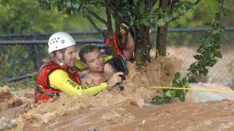 Edward Spark rescued from flooded Dent St by QFRS swift water specialist David Crichton during Toowoomba floods. Photo Nev Madsen / The Chronicle
