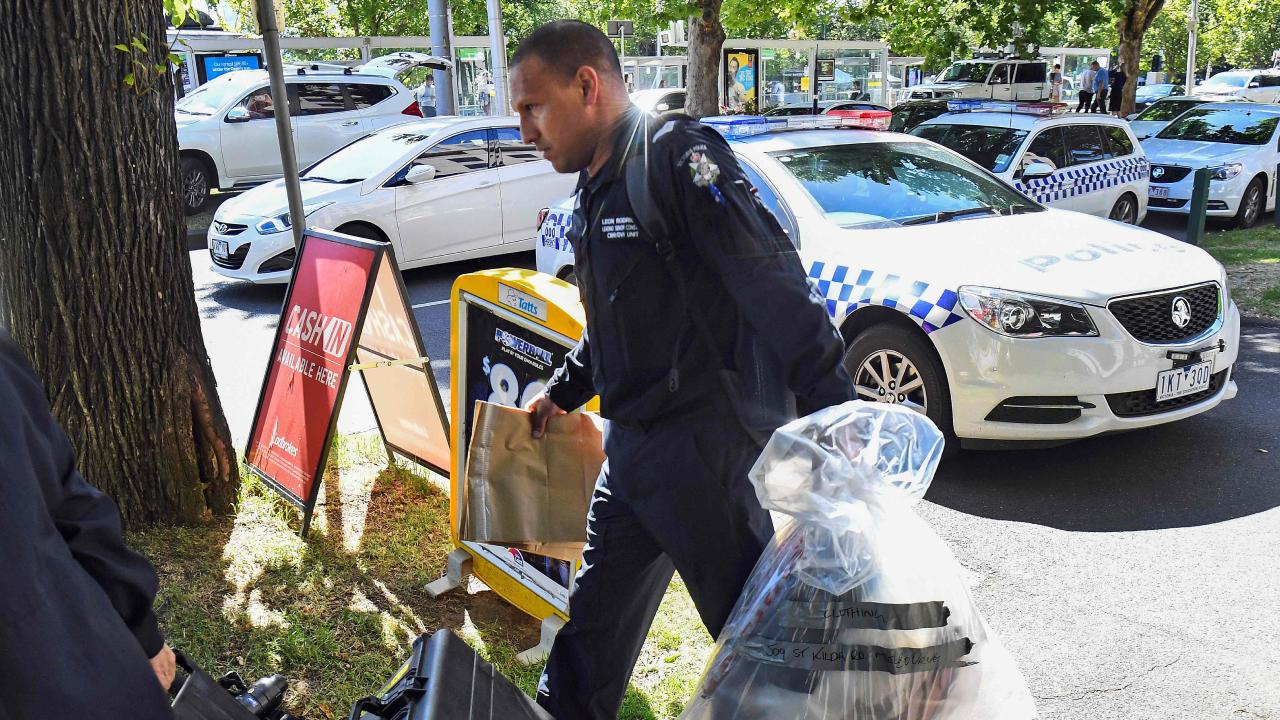 A Victoria Police forensic officer carries items to be loaded into a trailer outside the Italian consulate in Melbourne. Picture: William West/AFP