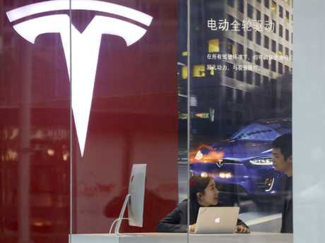 Workers seen in a Tesla store in Beijing, China, this week. Picture: AP