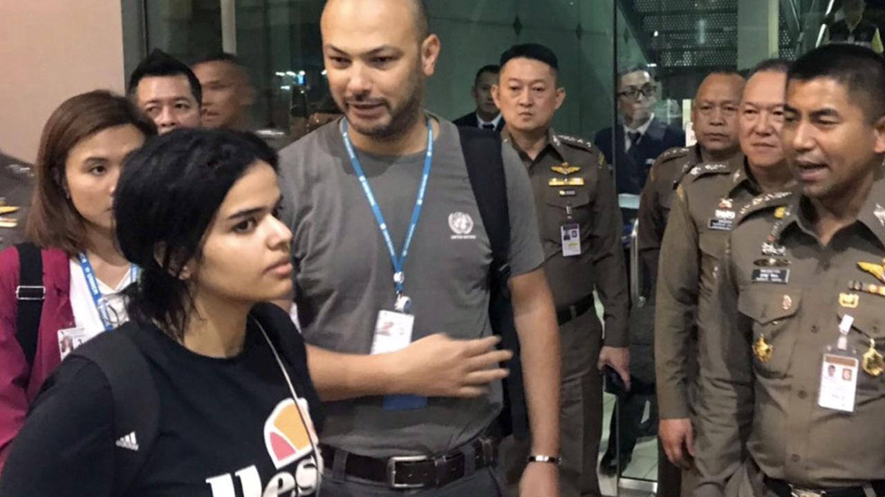 Saudi woman Rahaf Mohammed al-Qunun walks by Chief of Immigration Police Maj. Gen. Surachate Hakparn, right, before leaving the Suvarnabhumi Airport in Bangkok. Picture: AP