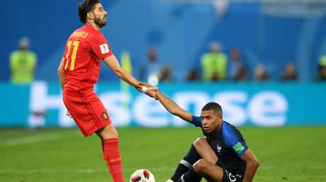 Yannick Carrasco of Belgium helps Kylian Mbappe of France to his feet during the World Cup Semi Final