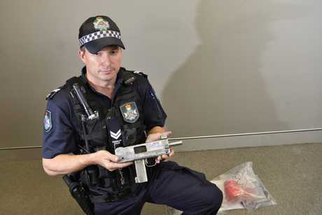 Darling Downs Tactical Crime Squad Senior Constable Michael Glover with the homemade submachine gun, a MAC-10, allegedly seized from a Harristown home.