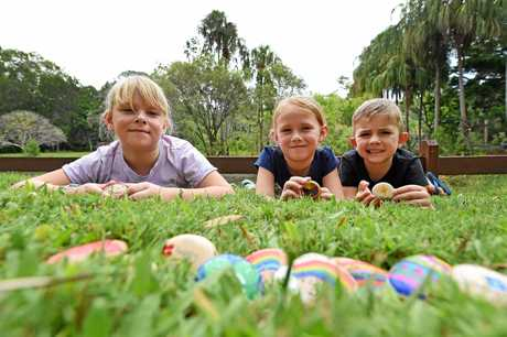 ROCK HUNTERS: Maddie Gallagher, 7, Hannah Gallagher, 4 and Tully Gardner 4 in Hervey Bay Botanical Gardens with rocks they decorated to drop them for others to find.