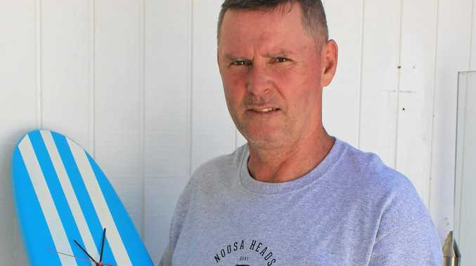 ALWAYS CREATIVE: Tommy Painter and one of his surfboard clocks.
