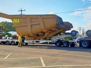 Wide load tips turning corner in small town