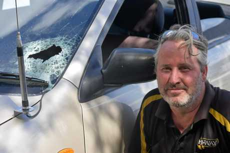 Ben Sisson with his Mazda 323 and its smashed-in windscreen.