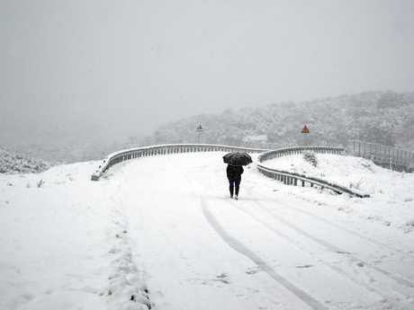 A woman passes a snow-covered bridge in Myrodafni village, northwestern Greece as temperatures plunge. Picture: AP