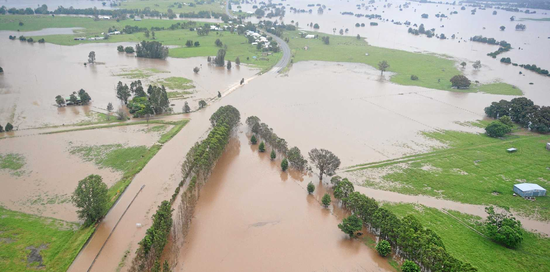 The PAcific Highway with water rushing across it at Swan Creek. Photo: Adam Hourigan / The Daily Examiner