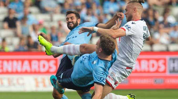 Ken Ilso Larsen of Adelaide has his shot blocked by Michael Zullo and Aaron Calver of Sydney FC. Picture: Steve Christo/AAP