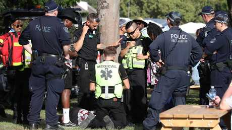 A man lying on the ground is treated by medics at the FOMO festival in western Sydney and taken away in a buggy for medical treatment. Picture: David Swift.