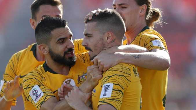 Socceroos players Aziz Behich (left) and Jackson Irvine congratulate Jamie Maclaren after he opened his scoring account for the national team against Palestine on Friday night. Picture: Getty Images