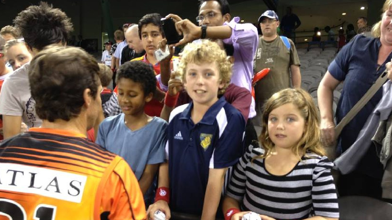 Mackenzie Harvey (centre) as an 11-year-old fan with Brad Hogg at the BBL.