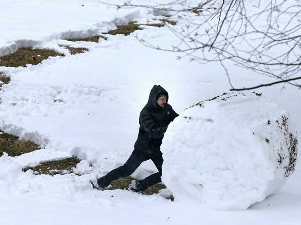 William Biscarri pushes snow into a large roll in Missouri. Picture: AP