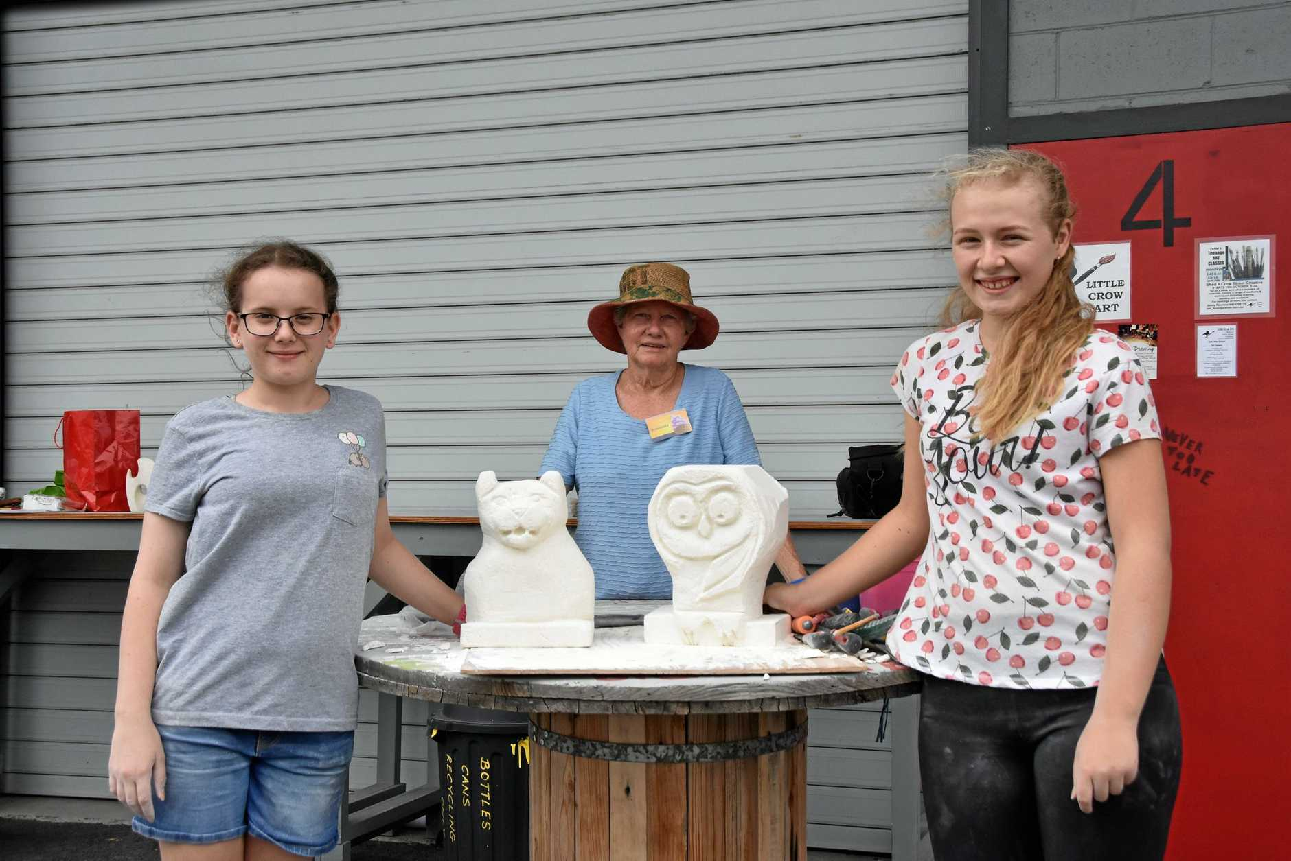Amity Roberts, 13 and Tamara Colebrook, 15 with local artist Rosemary Anderson at the Sculpture in Limestone workshop for SUNfest 2019.