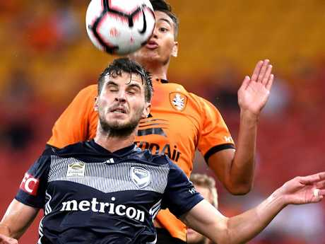 Brisbane Roar's Dane Ingham (back) jumps for the ball with Melbourne Victory's Terry Antonis on Tuesday night. Picture: Getty Images