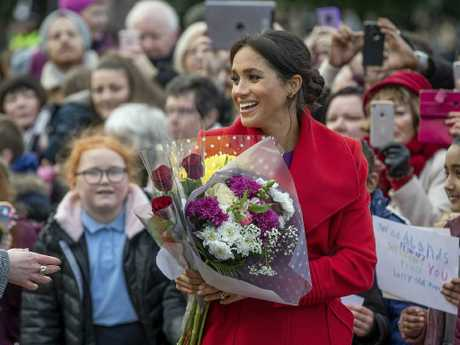 Meghan received flowers from the crowd. Picture: Charlotte Graham/AP