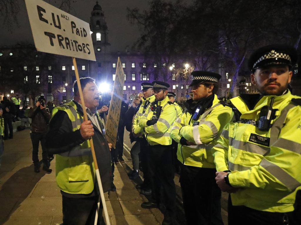 An pro-Brexit demonstrator confronts police officers in Parliament Square in London. Picture: AP