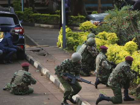 Kenyan armed forces and civilian people take cover after an attack on a hotel, in Nairobi, Kenya.  Picture:  AP