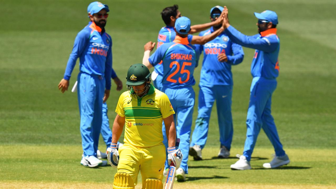 Aaron Finch walks while India celebrate. (Photo by Daniel Kalisz/Getty Images)