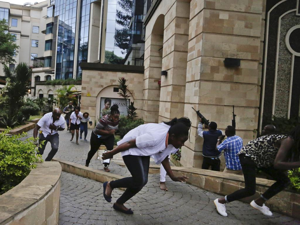 Civilians flee as security forces aim their weapons at the buildings of a hotel complex in Nairobi, Kenya, Tuesday, Jan. 15, 2019. Picture: AP Photo/Khalil Senosi