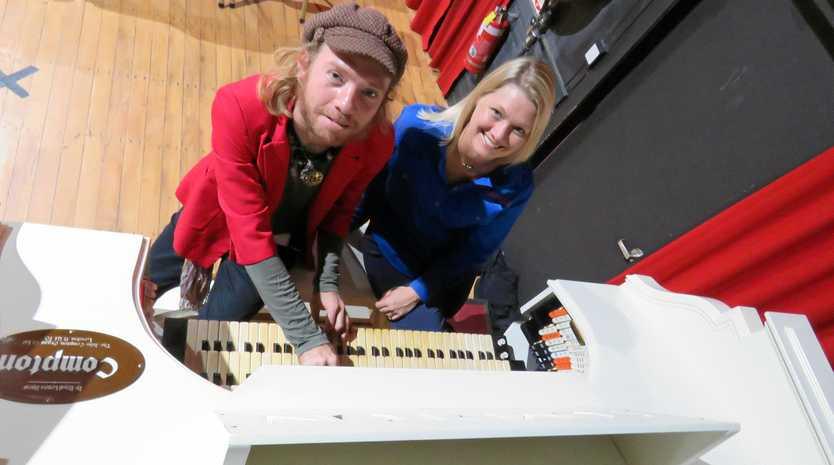 Harmony raises money: Musician Adro Kat and Drought Angels representative Monique Mahoney at Ron West's revered keyboard inside Pomona's Majestic Theatre.