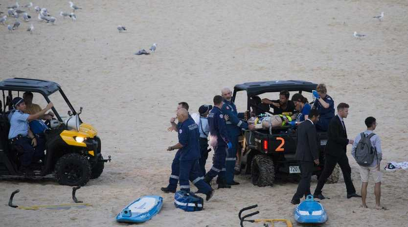 One of the men being assisted by emergency services after being caught in a rip at the southern end of Bondi Beach. Picture: Dylan Robinson
