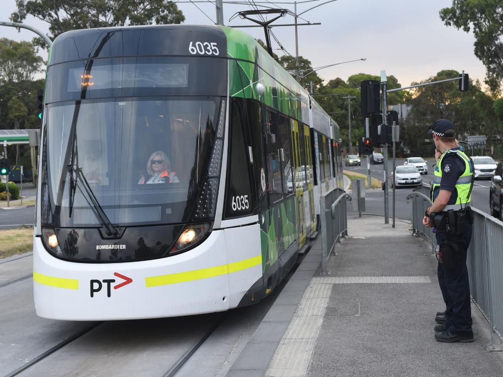 Police officers man tram stop 61 on Plenty Rd in Bundoora. Picture: Tony Gough