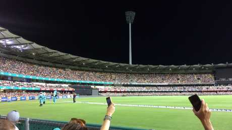 Fans at the Gabba use their phones to try to shed some light on the matter. Picture: John O'Brien