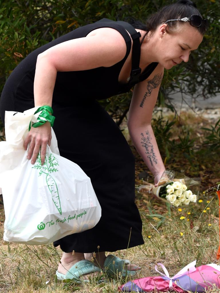 A woman places flowers at the scene. Picture: Nicole Garmston