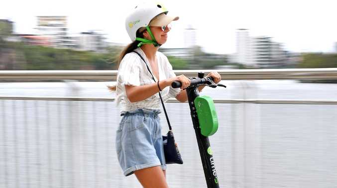 A woman rides a Lime scooter along the boardwalk in Brisbane's CBD. Picture: AAP/John Gass