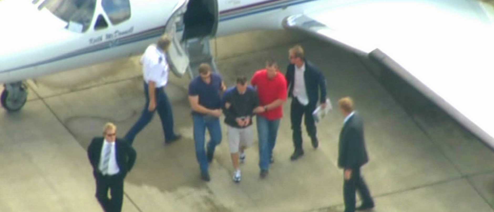 May 2007: Police escort Brendan Luke Karl Berichon off a chartered plane from Victoria to Brisbane.