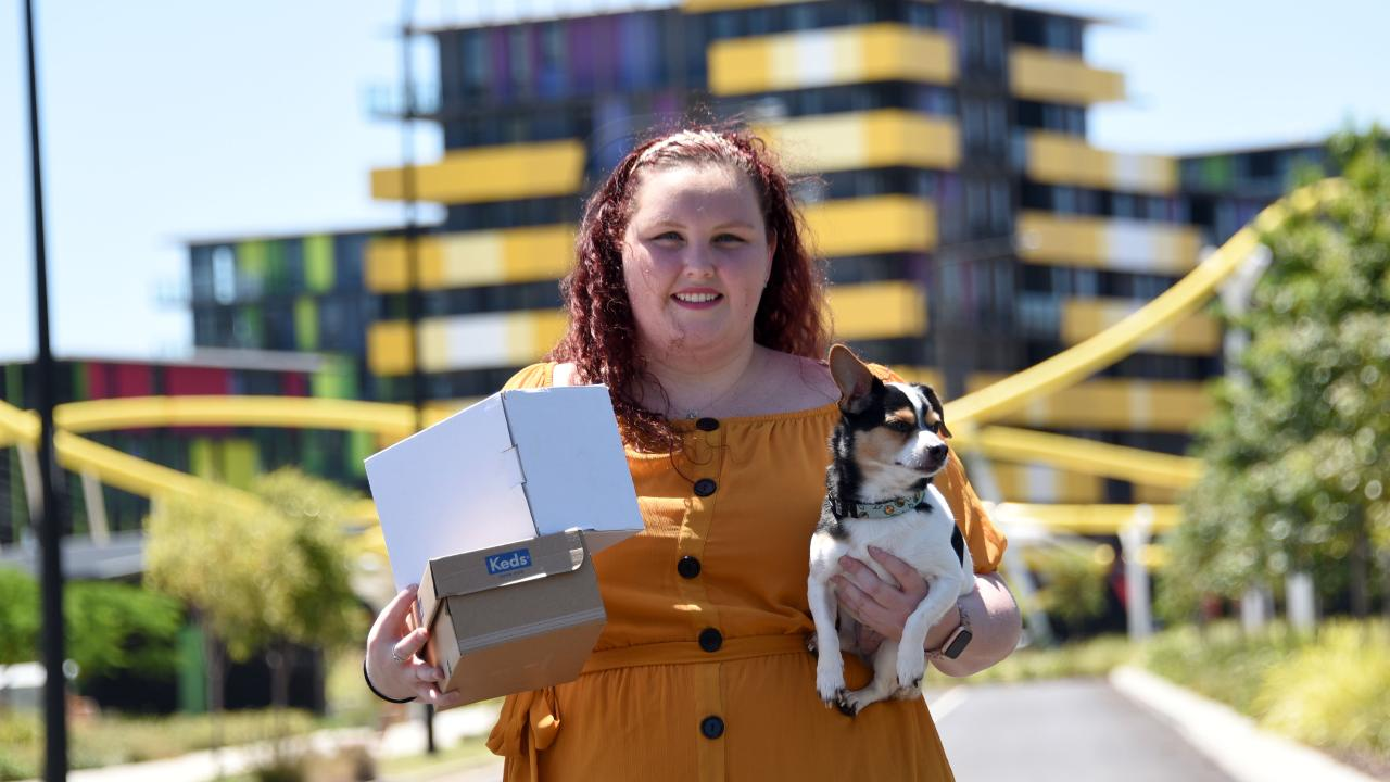 Nurse Georgia Johnson and her dog Duke are one of the first to move into the Smith Collective, the former Comm Games Village. (Photo/Steve Holland)