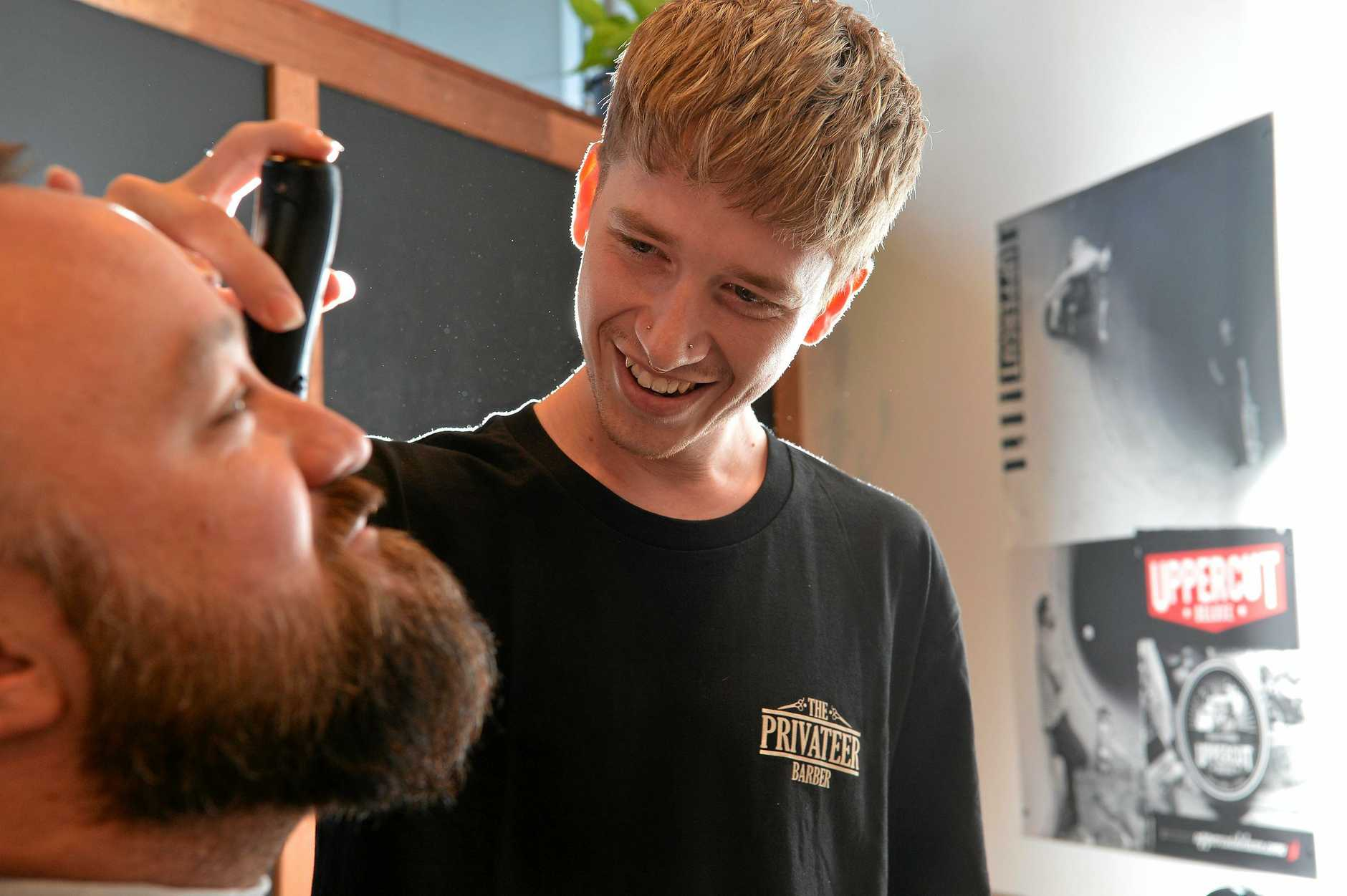 The Privateer Barber has opened in Currie Street  Harry the barber busy cutting hair and beards.
